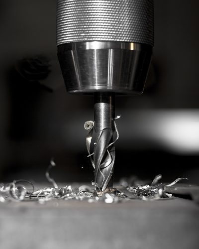 sharp metal dill in action drilling a hole in a metal plate